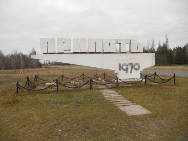 Sign for Pripyat - surrounded by radioactive warning signs