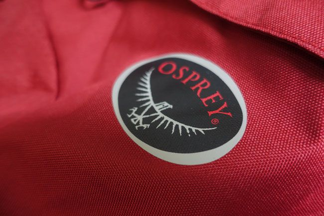 Close up of the Osprey logo on the red farpoint 80 backpack
